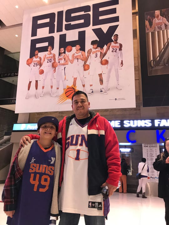 Jose Reyes, 28, of Glendale, with his son, Michael Angelo, 8, who are Mexican-American are longtime Suns fans. But they did not know their favorite player, Devin Booker is of Mexican descent.