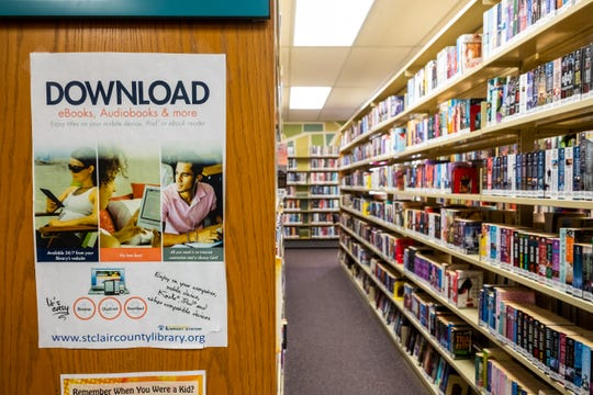 An advertisement for an app hangs on a bookshelf in St. Clair County Library's main branch in Port Huron. A discussion being had about developing a new location the branch has yet to come to any conclusions.
