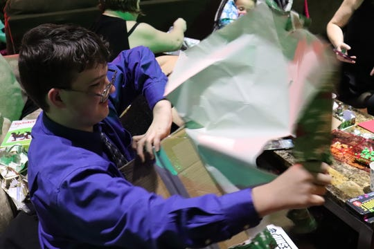Nolan, 15, opens a gift at 50 Christmases.