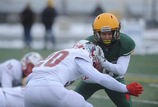Bishop Manogue's Colby Crisp (2) gets hit by Liberty's Isiah Revis during their playoff football game in Reno on Nov. 30, 2019.