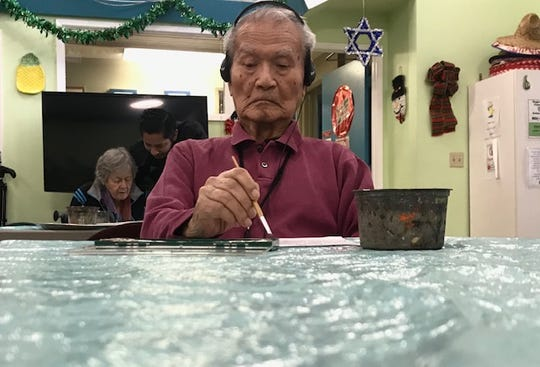 Clark Yamazaki, 89, of West Los Angeles paints a Christmas picture at OPICA Adult Day Care Services. He is a patient with UCLA's Alzheimer's and Dementia Care program.