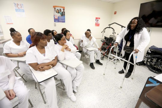 LaJune Wilson, a training associate at Selfhelp Community Services in Manhattan, demonstrates the proper use of a walker for Home Health Aide trainees.