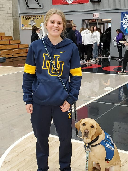 Nevada Union senior Reese Wheeler with her 3-year-old service dog Rover at Foothill High School on Dec. 13, 2019.