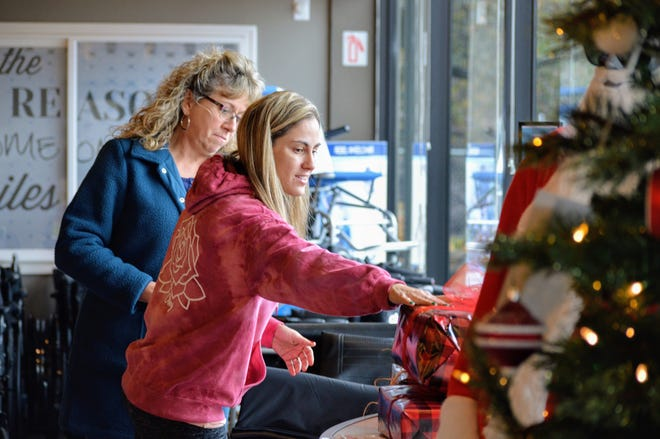 Gayle Adelman, right, helps a woman put her donated gifts by the Christmas Tree in inside Everything Medical on Friday, Dec. 13, 2019.
