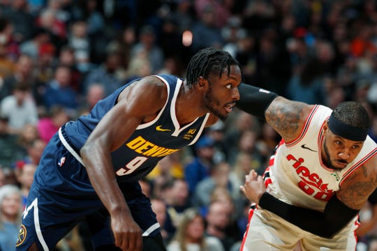 Denver Nuggets forward Jerami Grant, left, fights for position for a rebound with Portland Trail Blazers forward Carmelo Anthony in the first half of an NBA basketball game Thursday, Dec. 12, 2019, in Denver.