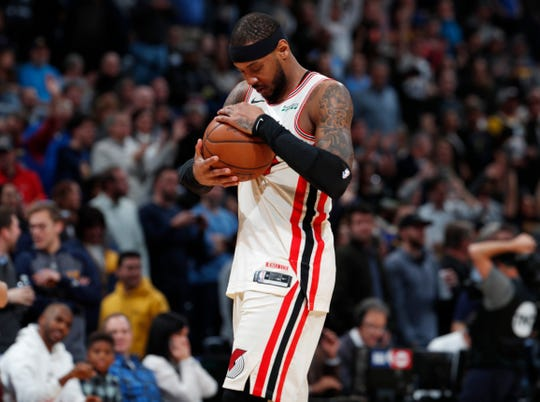 Portland Trail Blazers forward Carmelo Anthony cradles the ball before tip off against his former team, the Denver Nuggets, in the first half of an NBA basketball game Thursday, Dec. 12, 2019, in Denver.