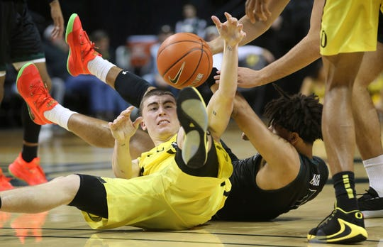 Oregon's Payton Pritchard, left, and Hawaii's Drew Buggs scramble for a loose ball during the second half of an NCAA college basketball game in Eugene, Ore., Saturday, Dec. 7, 2019.