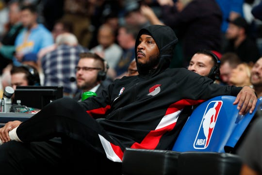 Portland Trail Blazers forward Carmelo Anthony sits on the bench as he awaits to be introduced in the first half of an NBA basketball game against his former team, the Denver Nuggets, Thursday, Dec. 12, 2019, in Denver.