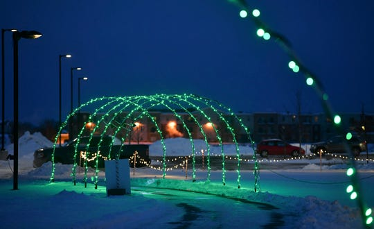 Lights form an archway over the path as part of the Country Lights Festival Wednesday, Dec. 11, 2019, in Sartell.