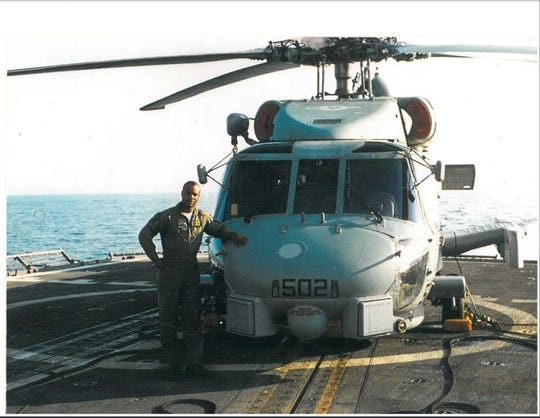 FAMU alum Lt. Reggie Williams of the U.S. Navy poses in front of an SH-60B Seahawk while on a ship in the Mediterranean Sea. He's retired from the service. Williams is cheering for the Midshipmen in the Army-Navy Game.