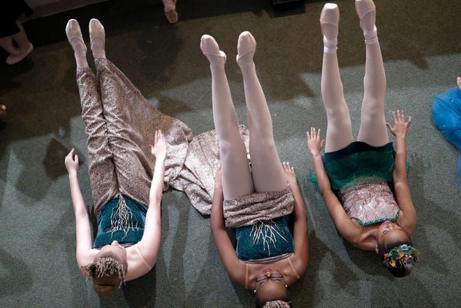 """Three dancers stretch together before the start of rehearsal for the Ballet Arts Conservatory of Tallahassee's """"Christmas in Narnia"""" at Lincoln High School Thursday, Dec. 12, 2019."""