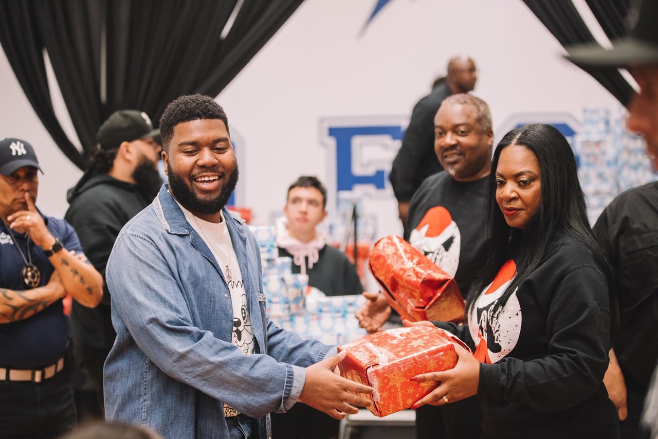 Khalid and his mother, Linda Wolfe, hand out Christmas gifts at Del Valle Middle School in 2019. The chart-topping singer and songwriter came to El Paso his senior year of high school and now calls the city home.