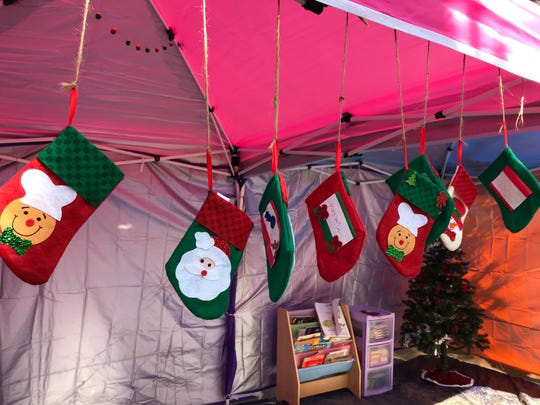 """Christmas stockings hang from the canopy of the """"escuelita,"""" or """"little school,"""" at the Chamizal Park in Juarez, where Mexican migrants are camped waiting for a chance to seek asylum in the U.S."""