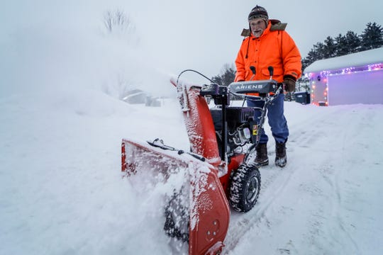 Jim Hanh, of Weston, clears snow off from his neighbor's driveway Thursday, Dec. 12, 2019. T'xer Zhon Kha/USA TODAY NETWORK-Wisconsin