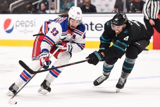 Dec 12, 2019; San Jose, CA, USA;  New York Rangers center Mika Zibanejad (93) controls the puck against San Jose Sharks defenseman Brenden Dillon (4) during the first period at SAP Center in San Jose.