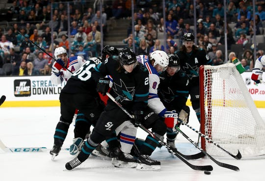 Marcus Sorensen #20 and Marc-Edouard Vlasic #44 of the San Jose Sharks go for the puck against Jacob Trouba #8 of the New York Rangers at SAP Center on December 12, 2019 in San Jose, California.