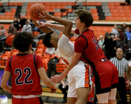 Burkburnett's Jaden Arnold is fouled by Plainview's Caleb Lusk Thursday, Dec. 12, 2019, in the Union Square Bulldog Classic in Burkburnett. The Bulldogs defeated Plainview 46-44.