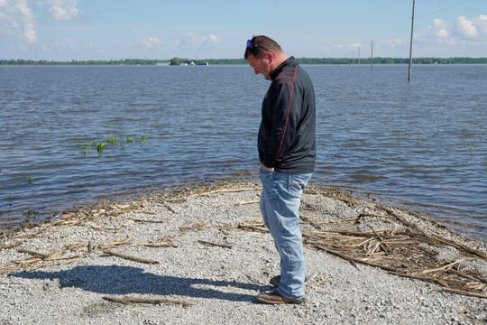 In this May 10, 2019 photo, Brett Adams stands where the road to his flooded farm disappears under flood waters, with the farm buildings visible in the background, in Peru, Neb. Adams had thousands of acres under water, about 80 percent of his land, this year. The water split open his grain bins and submerged his parents' house and other buildings when the levee protecting the farm broke.