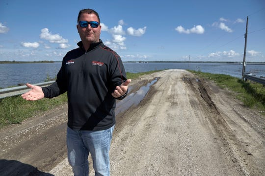 In this May 10, 2019 photo, Brett Adams gestures as he stands where the road to his flooded farm disappears under flood waters, with the farm buildings seen in the background, in Peru, Neb. Adams had thousands of acres under water, about 80 percent of his land, this year. The water split open his grain bins and submerged his parents' house and other buildings when the levee protecting the farm broke.