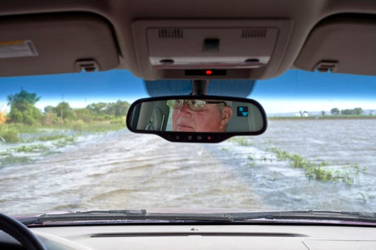 In this June 27, 2019 photo, Gene Walter, of Crescent, Iowa, drives his truck through a flooded road that sits between flooded fields in Crescent, Iowa. This year's record rainfall and devastating flooding are forcing tough decisions about the future of farming in in the face of climate change. Like many in the water-weary Midwest, Walter doesn't know if climate change was responsible for the second major flood in nine years. Or the increasingly frequent torrential rains that dump more water in an hour than he used to see in days.