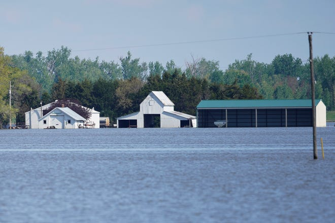 In this May 10, 2019 photo, farm buildings belonging to Brett Adams are surrounded by flood waters, in Peru, Neb. Adams had thousands of acres under water, about 80 percent of his land, this year. It split open his grain bins and submerged his parents' house and other buildings when the levee protecting the farm broke.