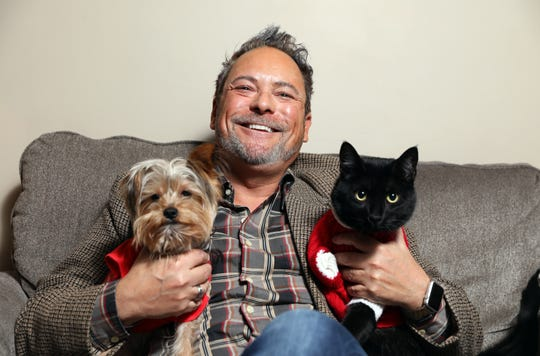 Steve Foreman, author and assistant superintendant at Zanesville City Schools, with two real-life characters from his books, Lee Lee the cat and Finley the dog. Both animals are missing a leg and are inspirational characters in his books.