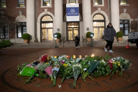 A woman walks past a make-shift memorial for Tessa Majors on the Barnard College campus on Thursday night.