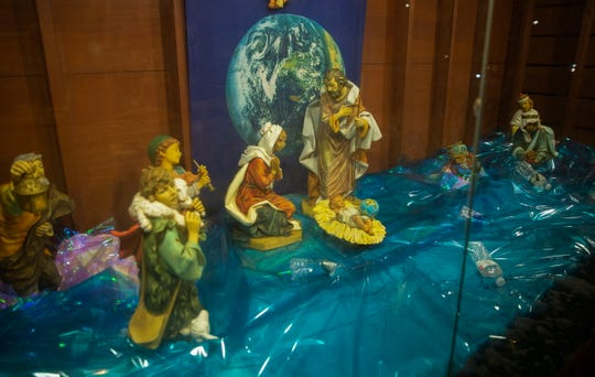 "A nativity scene on display outside of St. Susanna's in Dedham, Massachusetts, shows the Three Wisemen and animals underwater beneath a banner that reads ""God so loved the earth, will we?"" In years prior, the nativity scene has had other political themes including immigration issues and mass shootings."