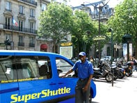 Airport Checkin -- SuperShuttle, a shared airport shuttle service, launched its first international service in Paris. Pictured is a SuperShuttle vehicle and its driver, Elie Tambou in Paris. Its service is available from Charles de Gaulle, Paris Orly and the local airport Beauvais to anywhere in Paris, including hotels and local residences.  (Via MerlinFTP Drop)