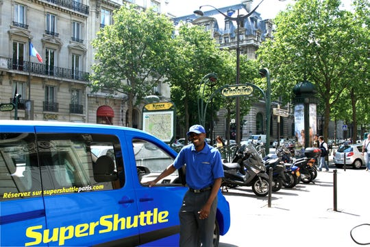 SuperShuttle, a shared airport shuttle service, launched its first international service in Paris. Pictured is a SuperShuttle vehicle and its driver, Elie Tambou in Paris.