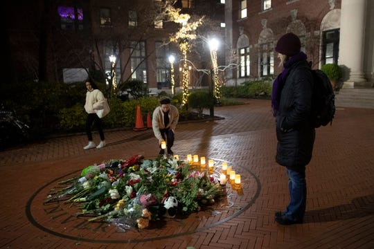 People pause and place a candle at a make-shift memorial for Tessa Majors inside the Barnard campus, Thursday, Dec. 12, 2019, in New York. Majors, a 18-year-old Barnard College freshman from Virginia, was fatally stabbed in a park near the school's campus in New York City.