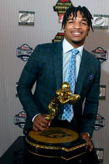 LSU's Ja'Marr Chase poses with the Biletnikoff Award after being named the nation's top receiver.