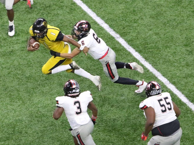 Ferriday quarterback Kobe Dillon (1) tries to run out of the grasp of Many defensive back Tackett Curtis (6) during the LHSAA Class 2A football state championship game at the Mercedes-Benz Superdome in New Orleans on Friday, December 13, 2019.