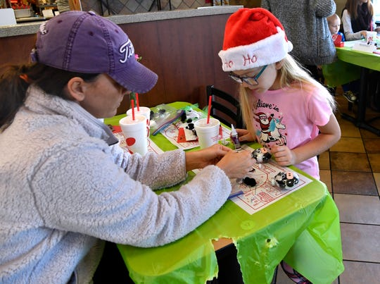 Lamree LaCaze, 8 makes a Christmas ornament with her mother Lacey Saturday morning during the Chick-fil-A Pajama Day at the South Clack Street restaurant.