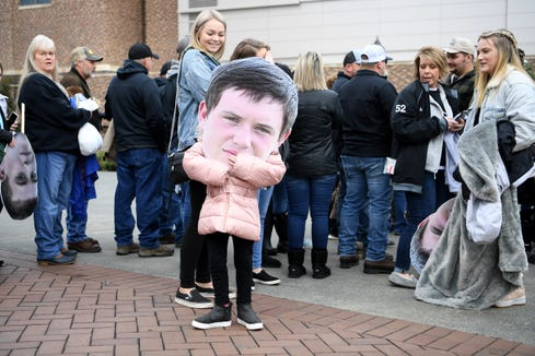 Kynnadi Odom, 7, plays with a giant cut out of her cousin, Robbinsville's Lex Hooper's, head as fans wait to be let into Wallace Wade Stadium for the NCHSAA 1A state championship game in Durham on Dec. 14, 2019. .