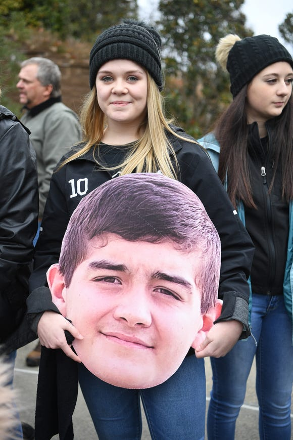 Robbinsville freshman Kinsley Odom carries a cut out of her boyfriend, Wade Hamilton's, head as she wait to be let into Wallace Wade Stadium for the NCHSAA 1A state championship game in Durham on Dec. 14, 2019.