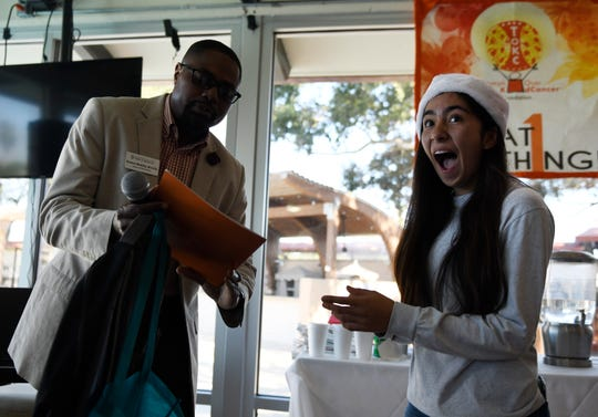 University of Texas' Ramon Blakley, left, awards Miller High School's Monique Cortez with a full tuition scholarship to the college, Saturday, Dec. 14, 2019. Cortez plans to study biology and work in the medical field.