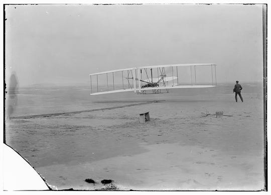 Photograph shows the first powered, controlled, sustained flight, Orville Wright at the controls of the machine, Wilbur Wright running alongside to balance the machine.