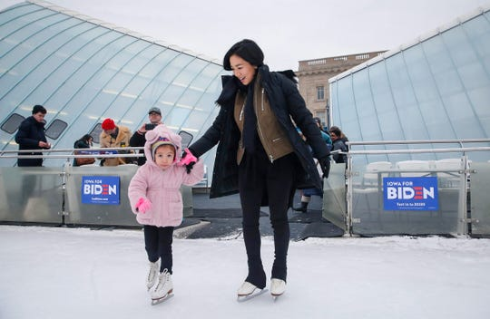 Avey Collins, 4, of Waukee leads Olympic figure skater Michelle Kwan onto the ice at Brenton Skating Plaza in Des Moines on Saturday, Dec. 14, 2019. Kwan, a supporter of Vice President Joe Biden, was in town to fire up support for Biden's run to be the democratic presidential candidate.