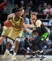 Oakland guard Kevin Kangu looks for an open pass as Michigan State guard Kyle Ahrens looks on during the game against Oakland at Little Caesars Arena in Detroit, Saturday, Dec. 14, 2019.