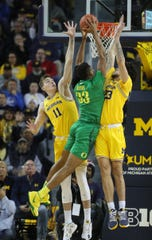 Michigan forward Colin Castleton, left, and  forward Brandon Johns Jr. defend against Oregon forward Francis Okoro (during first half action Saturday, December 14, 2019 at the Crisler Center in Ann Arbor, Mich.