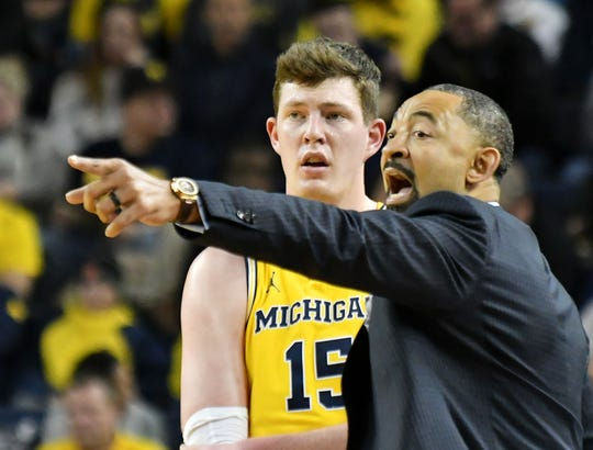 Michigan head coach Juwan Howard talks with Michigan center Jon Teske (15) in the first half.