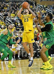 Michigan forward Brandon Johns Jr. (23) puts up a shot between Oregon guard Anthony Mathis (32) and Oregon forward Francis Okoro, right, in overtime.