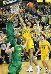 Oregon forward Francis Okoro, left, tips the ball away from Michigan forward Isaiah Livers (2) in the last seconds of the game.