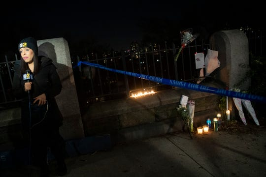 A reporter does a standup next to a make-shift memorial for Tessa Majors alongside Morningside Park, Thursday, Dec. 12, 2019, in Manhattan's Upper West Side,. Majors, a 18-year-old Barnard College freshman from Virginia, was fatally stabbed in a park near the school's campus in New York City. (AP Photo/Mary Altaffer)