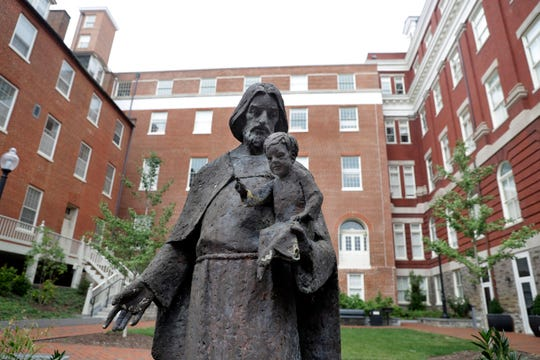 A Jesuit statue is seen in front of Freedom Hall, formerly named Mulledy Hall, on the Georgetown University campus in Washington. Georgetown University and two theological seminaries have announced plans for reparations to benefit descendants of the enslaved people who played a role in the institutions' success.