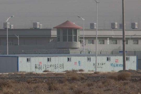 A guard tower and barbed wire fences are seen around a facility in the Kunshan Industrial Park in Artux in western China's Xinjiang region. People in touch with state employees in China say the government in the far west region of Xinjiang is destroying documents and taking other steps to tighten control on information.