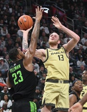 Oakland's Brad Brechting puts up a shot over Michigan State's Xavier Tillman in the first half.