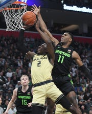 Oakland's Tray Moddox Jr. gets his shot blocked by Michigan State's Aaron Henry in the first half as the Michigan State Spartans take on Oakland University at Little Caesars Arena in Detroit, Michigan on December 14, 2019.