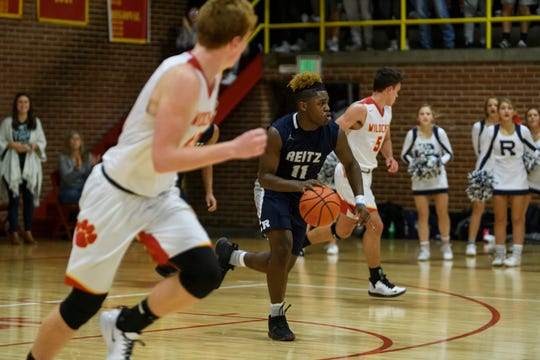 Reitz's Mar'Quon Givens (11) drives down the court during the fourth quarter against the Mater Dei Wildcats at Mater Dei High School in Evansville, Ind., Friday, Dec. 13, 2019. The Panthers made a huge comeback in the fourth quarter to defeat the Wildcats, 79-73.